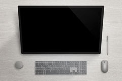 Big touch screen display on gray surface board. Pen, mouse, keyboard and dial beside Royalty Free Stock Photography