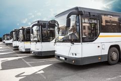 Tourist buses on parking. Big tourist buses on parking on the background of cloudy sky stock photo