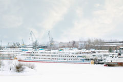 Big tourist liner and other ships on frozen river at winter Stock Photo