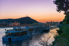 Big touristic steamboat on Danube at sunset. With cityscape of Budapest on the background Stock Photos