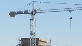 Tower crane works on building a house. Big Tower crane works on building a house stock video footage