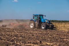 Big tractor plows the field and removes the remains of previously mown sunflower. Work agricultural machines Royalty Free Stock Photos