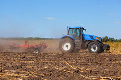 Big tractor plows the field and removes the remains of previously mown sunflower. Work agricultural machines Royalty Free Stock Image