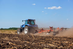 Big tractor plows the field and removes the remains of previously mown sunflower. Work agricultural machines Royalty Free Stock Photography