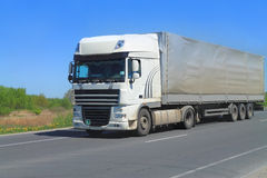 A Big Tractor Trailer Truck with semitrailer. A White Big Tractor Trailer Truck with semitrailer on a country road Stock Photo