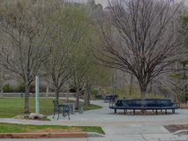 Park Benches and pathways in Memory Grove Park in Salt Lake City Utah along the Wasatch Front Rocky Mountains in early spring. Big Trees with Park Benches and Royalty Free Stock Photo