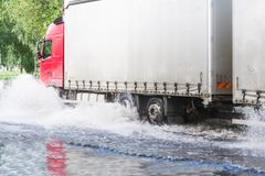 Big truck going through flooded street in town Gomel in Belarus stock images