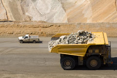 Big truck, little truck. A dump truck carrying 250 tons of rock dwarfs a pickup truck as it passes royalty free stock image