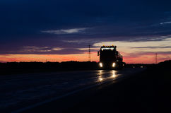 Big truck wagon rides on the road at sunset and sky with clouds Royalty Free Stock Photography