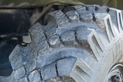 Big truck wheel a black tires closeup. Wide tires with deep protector for off road cars and trucks. Big truck wheel a black tires closeup. Wide tires with deep royalty free stock image
