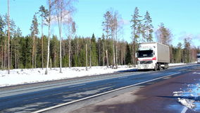 Big trucks passing by the road. Still with snow on the side and pine trees stock video footage