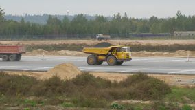 Big trucks rides on road. Truck is transporting material. Construction, concreting of airport runways, roads. Tippers stock video