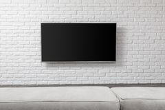 Big TV on the white wall. Living room led tv on white wall royalty free stock photography