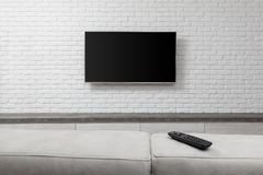 Big TV on the white wall. Living room led tv on white wall royalty free stock image