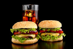 Big two cheeseburgers with glass of cola on black wooden table Royalty Free Stock Photography