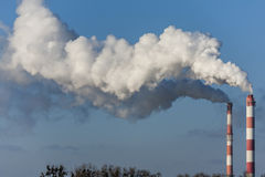Big two chimneys with dramatic clouds of smoke. Stock Photos