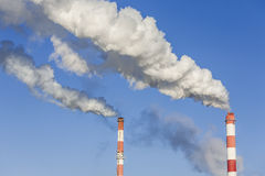 Big two chimneys with dramatic clouds of smoke. Stock Image