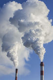 Big two chimneys with dramatic clouds of smoke. Royalty Free Stock Image