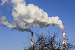Big two chimneys with dramatic clouds of smoke. Royalty Free Stock Images