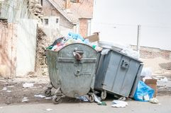 Big two metal dumpster garbage can full of overflow litter polluting the street in the city.  royalty free stock photo
