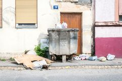 Big two metal dumpster garbage cans full of overflow litter polluting the street in the city with junk.  Stock Image