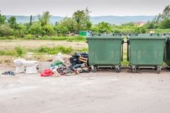 Big two metal dumpster garbage cans full of overflow litter polluting the street in the city with junk.  Royalty Free Stock Images