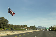 Big U.S. Flag By Freeway. A large US flag waves at passers- by on interstate 5 near Anderson, California Stock Photos