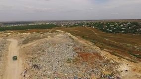 Big Urban Waste Dump At Suburbs In Ukraine. In the frame there is an aerial view over big urban waste dump with city buildings in greenery in a distance.  There stock footage