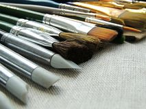 Big variety of brushes, tools for painting and sculpture on linen fabric background. Stock Images