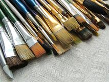Big variety of brushes, tools for painting and sculpture on linen fabric background. Stock Photos