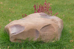 Big and very heavy stone boulder in the grass Stock Images