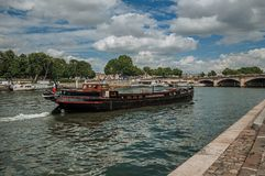 """Big vessel and boats anchored at the Seine River bank with trees under a sunny blue sky in Paris. Known as the """"City of Light"""", is one of the most Royalty Free Stock Photography"""
