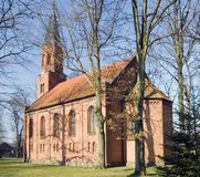 Big village church. A big church of Slowino, Poland. Some barren trees, pretty blue sky. Gothic style Stock Photo