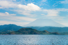 Big volcano rise over the island and sea Stock Photos