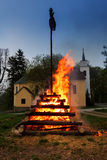 Big walpurgis night fire with witch on pile behind the church Royalty Free Stock Photography