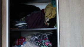 Big wardrobe with many clothes on the shelves at home stock video footage