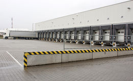 Big warehouse. Unloading big container trucks at warehouse building Stock Photos