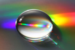 Big water droplet with rainbow. A giant water droplet reflects and refracts incident light forming beautfiul rainbow reflections. Shallow D.O.F with focus stock photography