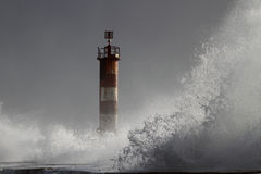 Big wave against beacon Stock Images