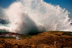 Big wave breaking on rocks Stock Photography