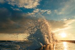 Big Wave Breaks About A Breakwater Against Sunset Background Royalty Free Stock Image