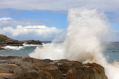 Big wave clashes upon spanish rocks. During flood large clear waves of the Atlantic Ocean are clashing upon the rocks along the west coast in Galicie in Spain Stock Images