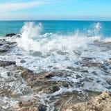 Big wave crashing on the rocks Stock Photo