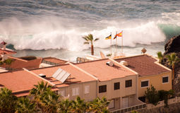 Big wave in front of some houses at the coast;. Big wave in front of some houses at the coast at tenerife Royalty Free Stock Image