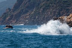 Big wave splashing against rocks. Big wave splashing against the rocks in the Gulf of Porto, Corsica royalty free stock image