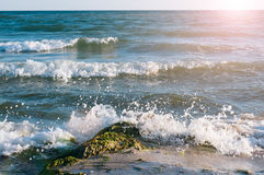 Big wave splashing. Sea water beating against the rocks and cliffs. Blue sky above the beach in the sun zenith refreshing drops of ocean water royalty free stock photos