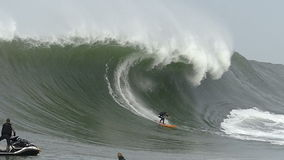 Big Wave Surfer Tyler Fox Surfing Mavericks California. Big wave surfer Tyler Fox surfing a giant wave at Mavericks surf break in Half Moon Bay, California USA