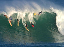 Big Wave Surfing in Hawaii. A group of surfers attempt to ride a huge wave while surfing at Waimea Bay on the North Shore of the island of Oahu in Hawaii Stock Photography