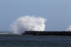 Big wave. S against beacon and pier of Ave river mouth, Vila do Conde, Portugal Royalty Free Stock Photography