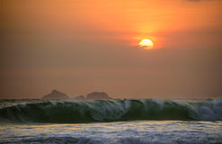 Big waves of Atlantic ocean at Ipanema beach and beautiful sunset with clouds and orange sky, Rio de Janeiro Stock Photo